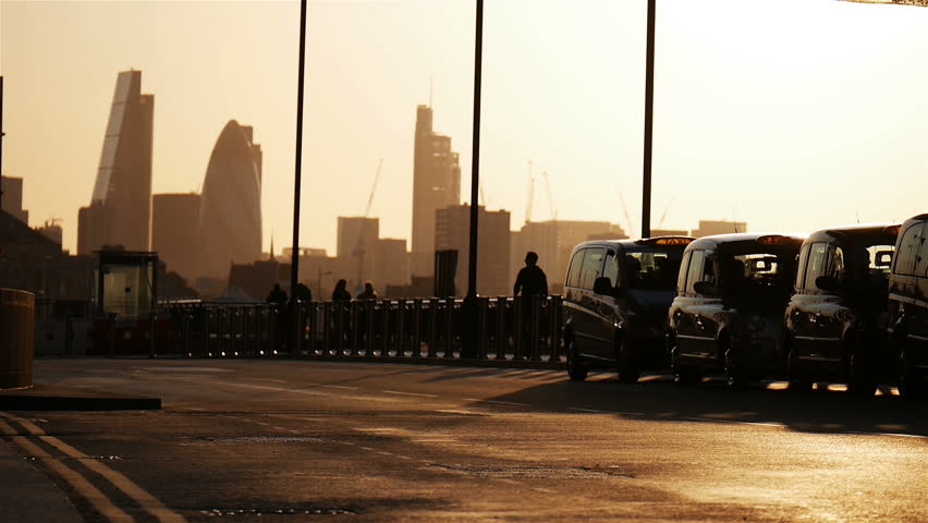 Dusk scene of London black cab taxis with the London skyline in the background while traffic, cyclists and pedestrians pass by in the foreground. Half speed, low angle video footage, no audio.