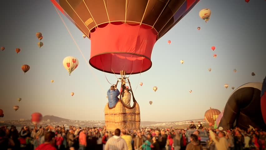 Spectators watching a hot air ballon departing with family in an annual festival
