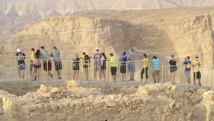 MASADA, ISRAEL - May 15, 2015: Group of young tourists enjoying on  on the highest point of the mountain. Masada, Israel, 2015.