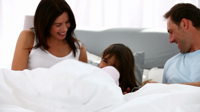 Happy family playing together on a bed - HD stock video clip