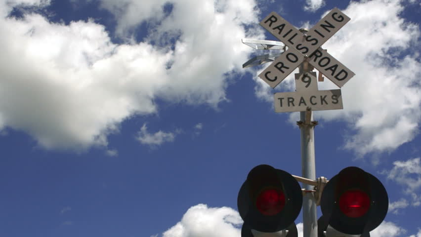 A train trips the red light warning signal while switching cars in a Texas town - HD stock footage clip