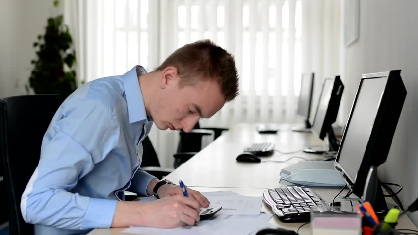 Man working in the office - writing on paper with pen and counting on a calculator - documents | Shutterstock HD Video #10103549