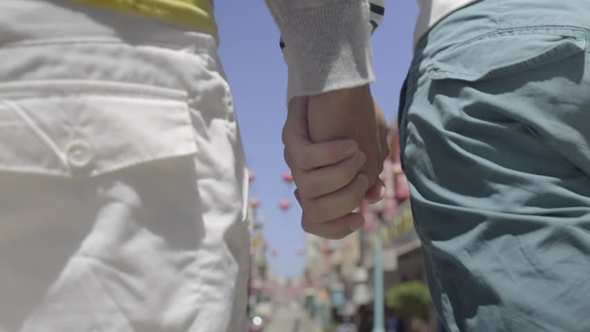 Closeup On Hand Holding Multiracial Gay Couple Walking Down The Street In Chinatown, San Francisco