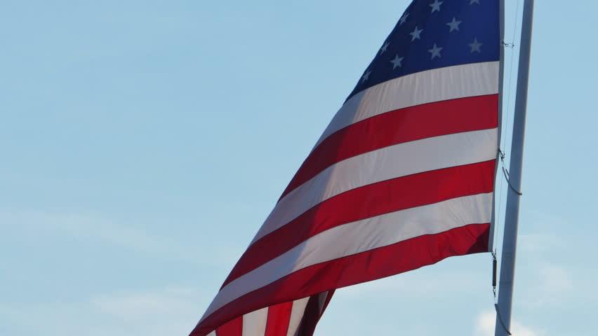 American Flag Blowing in the Wind Blue Sky - 4K stock video clip
