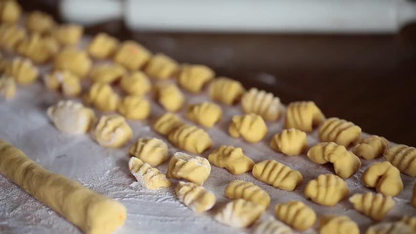 Video clip of woman cutting pasta for gnocchi on a wooden board.