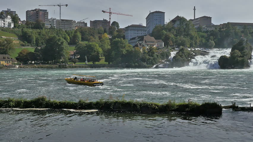 Yellow tour boat on the Rhine river below the Rhine Falls in Switzerland with city buildings in background.  - HD stock video clip