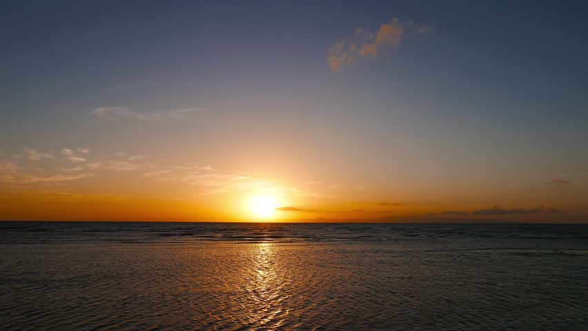 A sunrise video with clear skies from Dumaguete City, Negros Oriental, Philippines. Sun can be seen just above the horizon over subtle waves. Presented in real time.