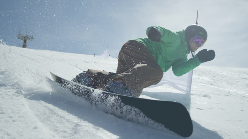 Slow motion close up snowboarder carving on perfectly