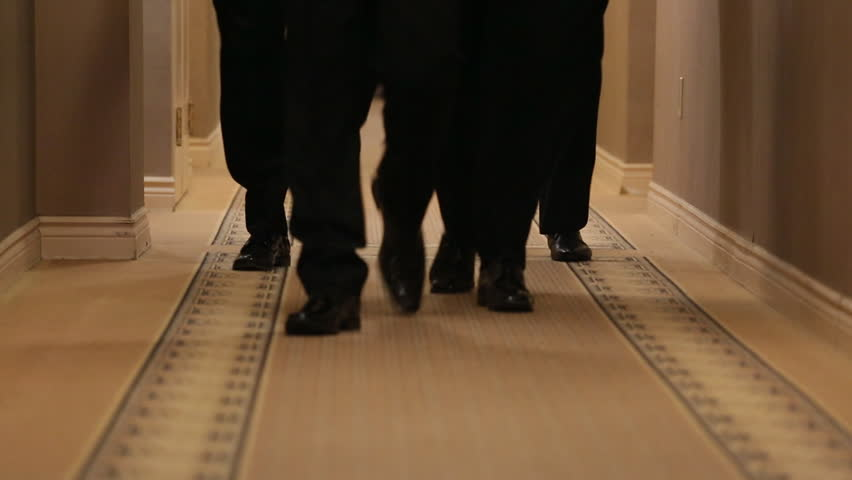 Four pairs of mens feet walking on carpet in black shoes