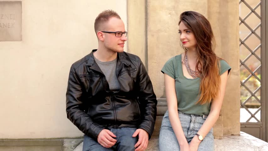 Young brown hair girl sitting on the street and talking with boy with glasses. They are smiling   Shutterstock HD Video #10224113