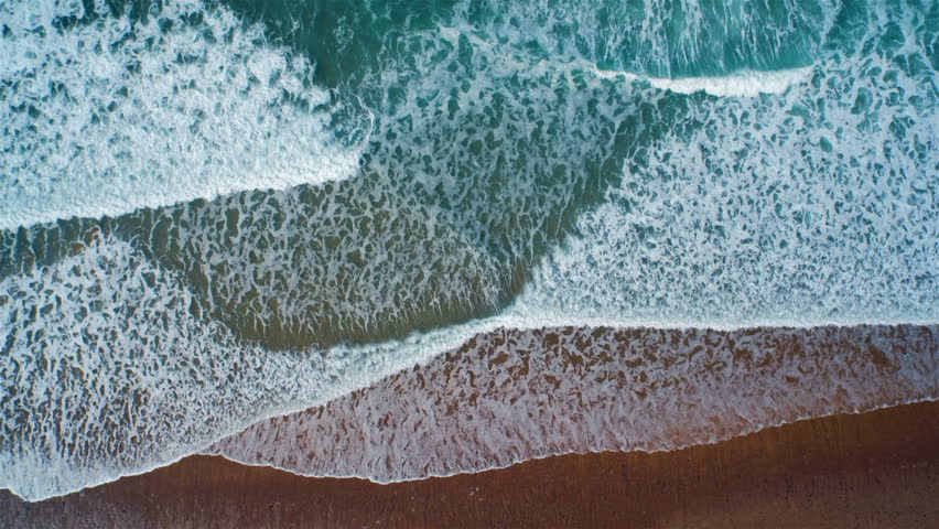 Aerial drone slow motion footage of ocean waves reaching shore. Lockdown shot of sea waves creating a texture from the white sea foam. Footage is filmed from an overhead perspective. HD 1080 video.