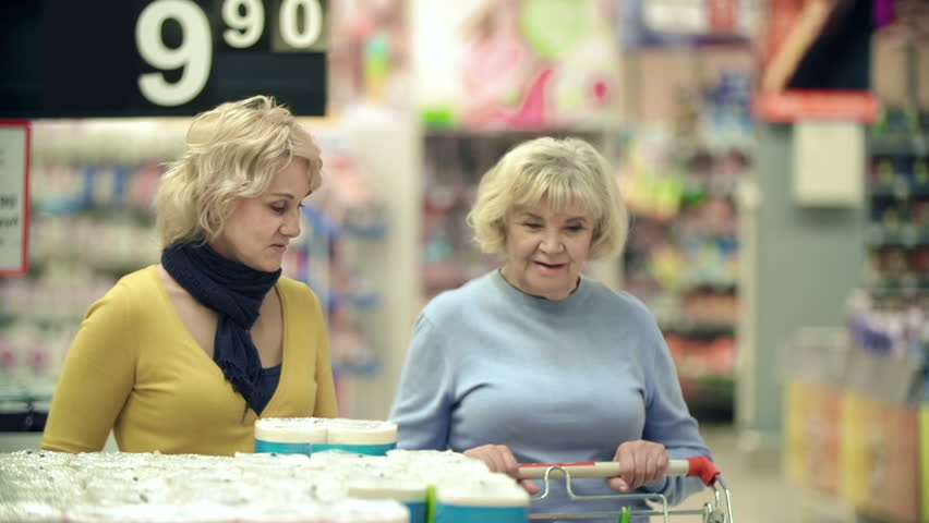 Close up of two women picking toilet paper and putting it into shopping cart