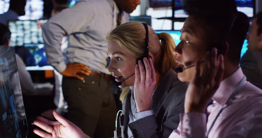4K Security & surveillance team working in a busy system control room. Could be a meteorological weather station or airport traffic control room.