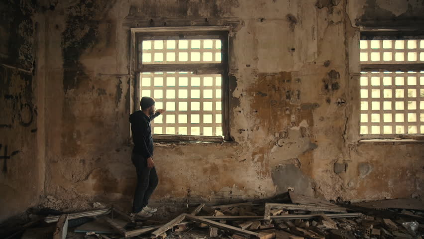 A ,troubled young man wearing a hood in an empty, wrecked,abandoned building, in mental suffering agony and remorse.Slow motion shot with tracking motion.