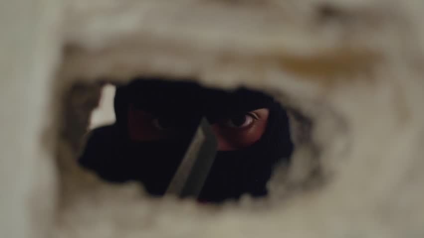 Ninja assassin,masked killer with knife lurking behind a crack in the wall.A ninja assassin lurks behing a crack in the wall with eyes wide open.Close up slider tracking shot.
