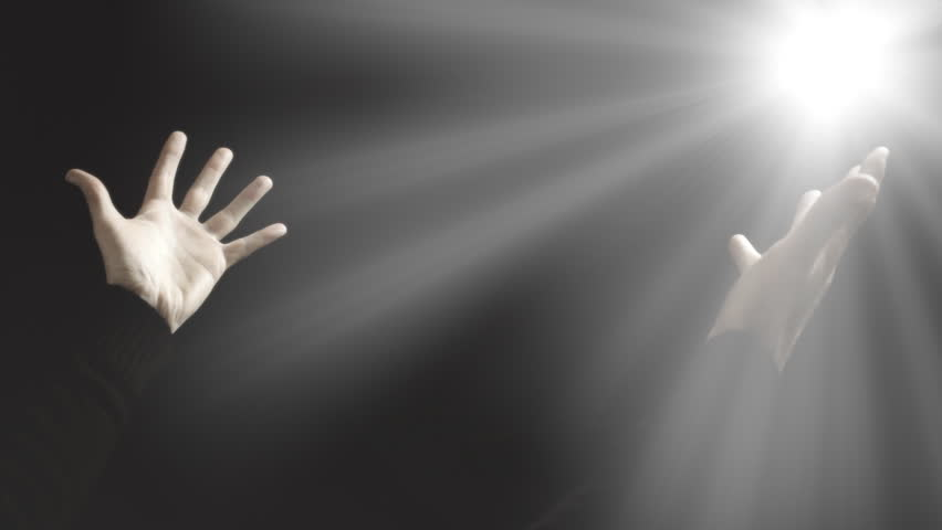 The wrinkled praying hands of an old man raising to Heaven, reaching for the mystical divine spirit in the sky; faith, hope, love, religion. A shiny light appears.