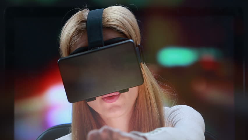 Car simulator using virtual reality technology. Girl with pleasure uses head-mounted display.