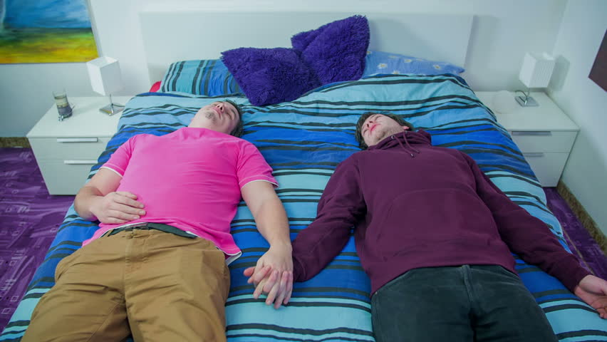 Gay Couple Lying On A Bed And Holding Hands While Talking