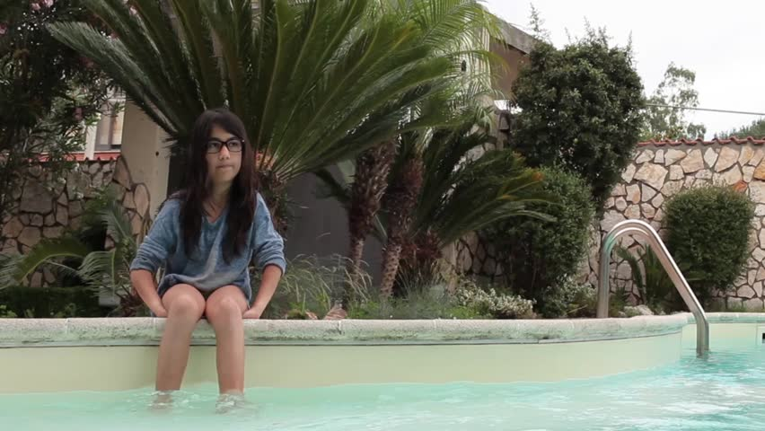 Cute Caucasian girl relaxing on the board of the swimming pool with feet in the water.