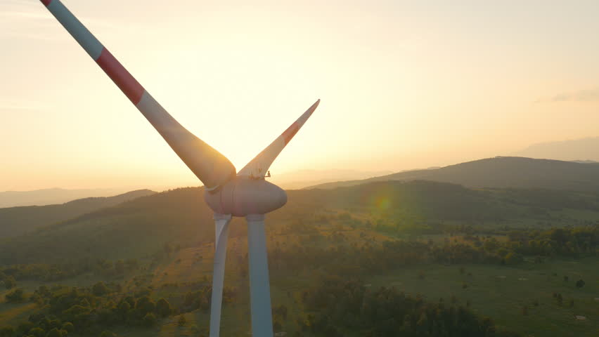 Aerial - Wind turbine blocking the sun with propeller at sunset - 4K stock video clip