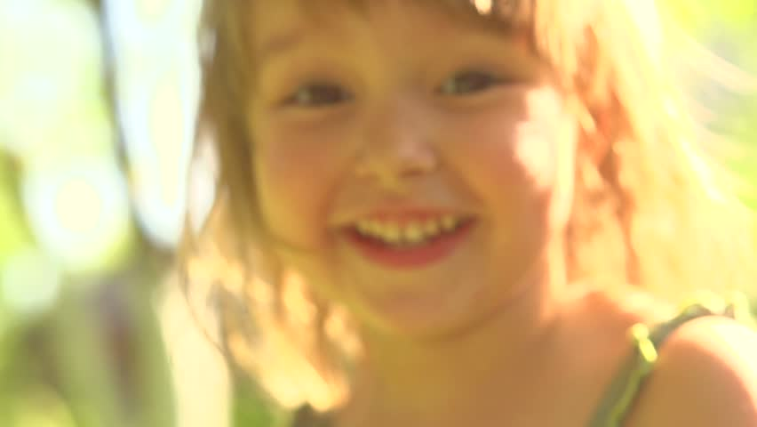 Portrait of a smiling little girl close up. Cute three years old child enjoying nature outdoors. Healthy carefree kid playing outside in summer park. Full HD 1080p. High speed camera, slow motion