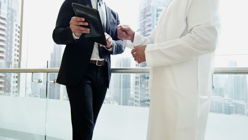 Western Caucasian Arabic male business banking finance technology tablet