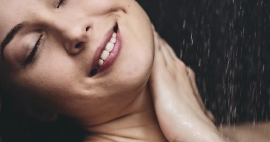Woman taking shower in slow motion dolly shot. Filmed in 4K DCi resolution. Young beautiful woman taking a shower gently touching her skin. Close up on neck and shoulder. Beauty and relax concept.
