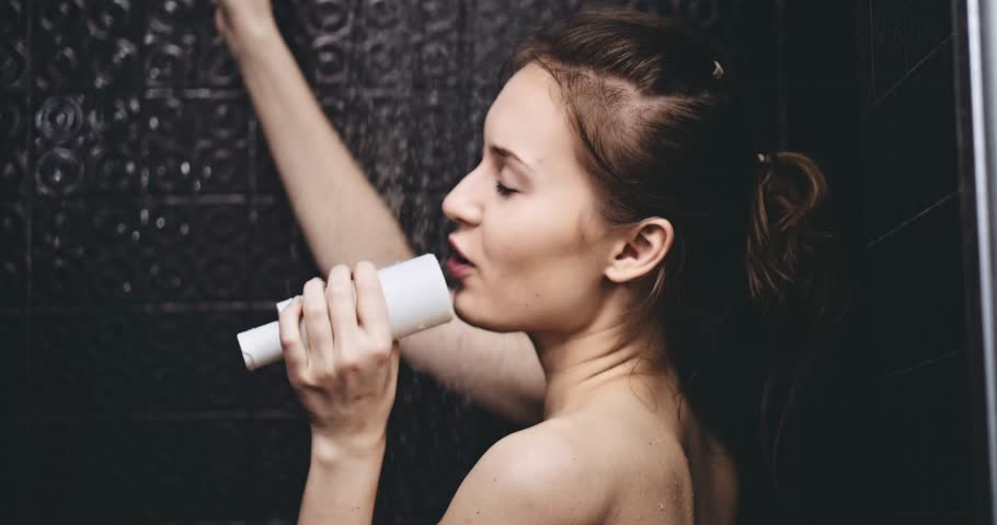 Young happy woman taking a shower and singing in a shampoo bottle as a microphone. Fun in daily life. Filmed in slow motion 120fps 4K DCi RAW.