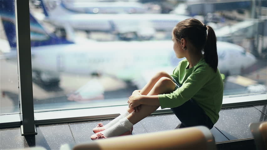 Child in airport near window looking on airplanes and waiting for time of flight
