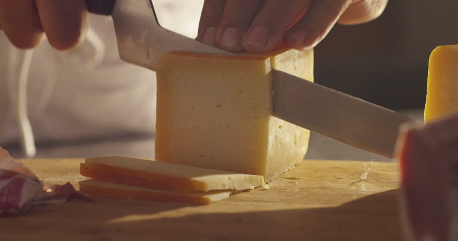 Super slow motion macro of a middle aged chef cutting cheese with knife on wooden board on restaurant kitchen table (extra close up)