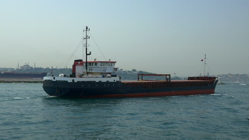 Dry cargo ship sailing into calm sea. Cargo ships are intended basically for carrying of bulk cargoes such as coal and timber. 4K Tracking shot of a general cargo ship