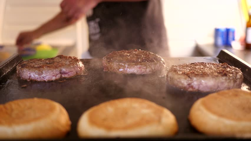 Cooking burger - roast meat cutlet at food fest - 4K stock footage clip