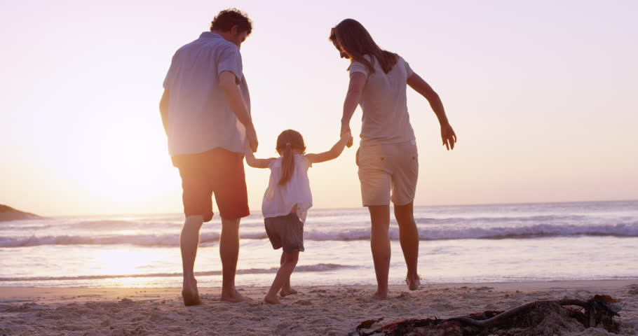 Happy family on the beach holding hands swinging little girl around at sunset on vacation slow motion RED DRAGON