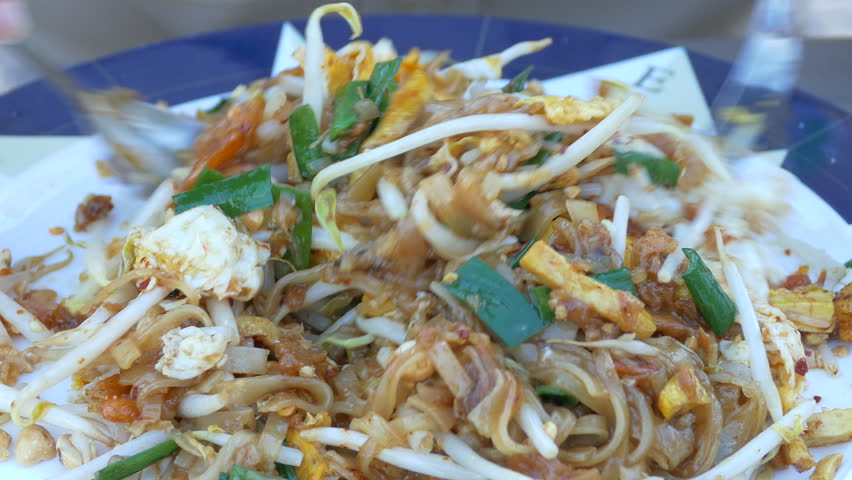 hand eating Pad Thai stir-fried rice noodles with eggs and vegetables ...