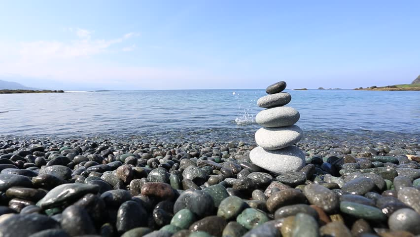Stones balance, pebbles stack over blue sea in Crimea. Blue sky on sunny coast in summer - HD stock footage clip