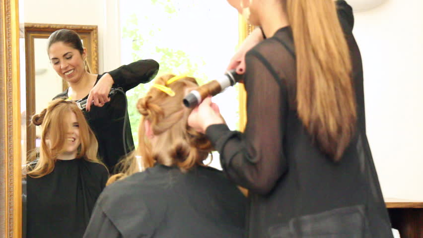 Rear View of Young Unrecognizable Woman with Long Red Hair Having Hair Styled in Curls by Stylist in Salon