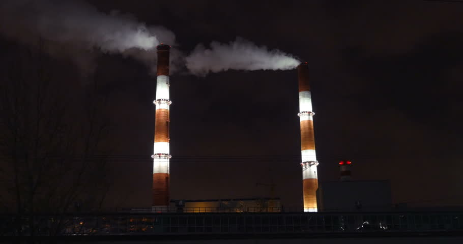 Two huge smoking factory pipes illuminated at night. Industry, manufacture and air pollution in the city - 4K stock footage clip