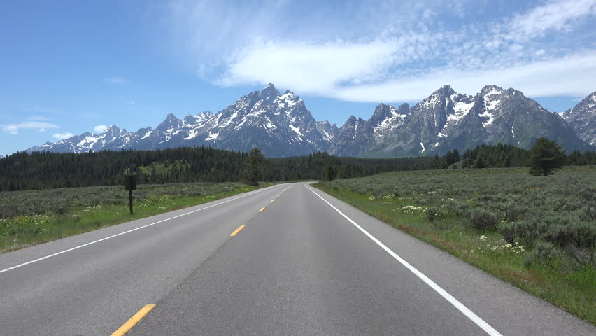GRAND TETON, WYOMING - APR 2015:  Drive POV beautiful Grand Teton Mountain range 4K. Point of view vacation travel. South of Yellowstone. Pristine wonder and beauty. Wildlife tourism destination. | Shutterstock HD Video #10530176