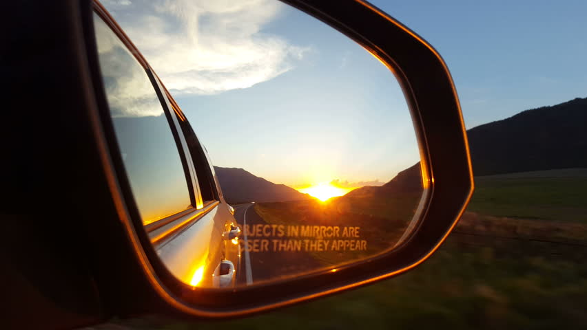 SANPETE COUNTY. UTAH - JUNE 2015: A beautiful orange and yellow sunset glows in the rear view mirror of an eastbound auto as it drives through a low mountain pass | Shutterstock HD Video #10530941