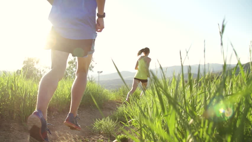 Couple Trail Running Outside At Sunset Slow Motion