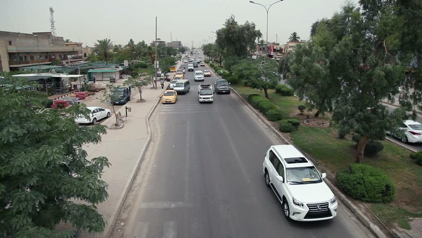 Car traffic and pedstrians on Palestine Street in Baghdad, Iraq