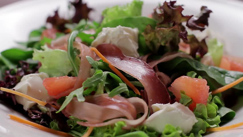 Delicious salad sprinkled with parmesan cheese. Close-up of salad ingredients.