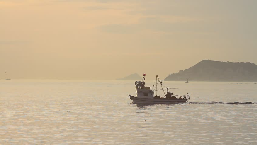Fishing boat cruising on sunset. Fisher vessel sailing into Marmara Sea towards Izmit Bay. Tracking Shot