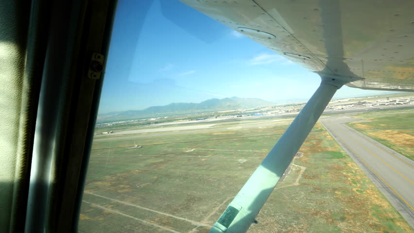 Looking out window to wing of small, prop plane as it departs. - 4K stock footage clip