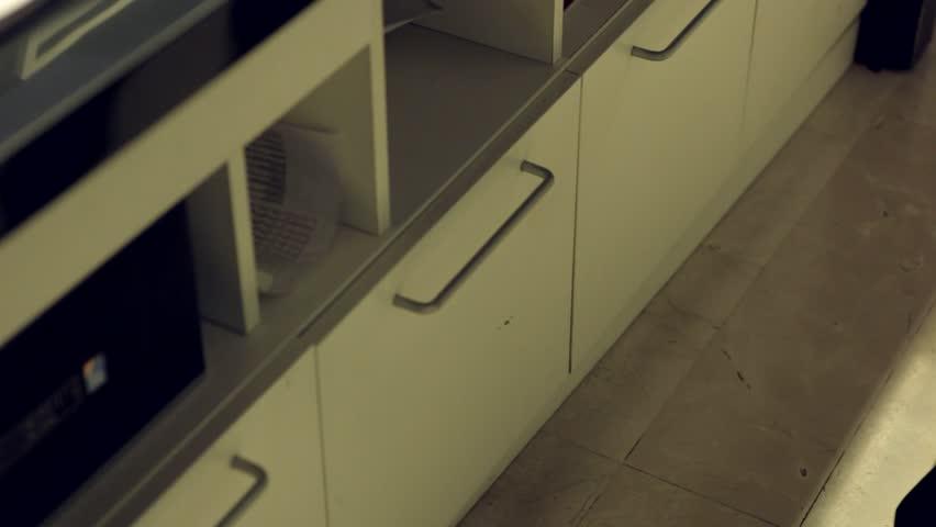 Businessman opens filing cabinet drawer, files folders