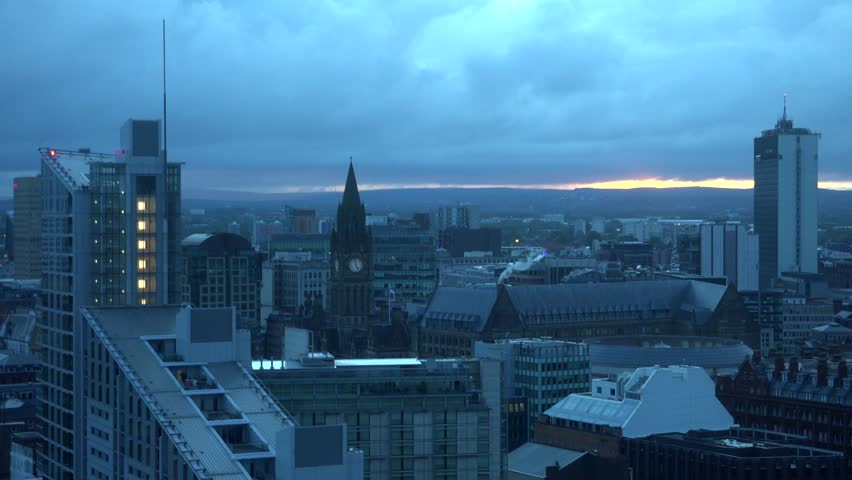 ULTRA HD 4K Timelapse of Manchester city panorama with cloud pass at sunset or sunrise, sun silhouette by day