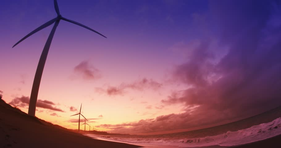 Beautiful subset in sea shore with many wind mill turbines spinning and generating clean energy. Ecological background - 4K stock video clip