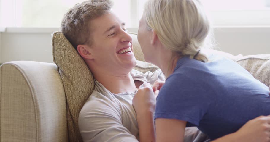 Young couple cuddling and talking on couch - 4K stock footage clip