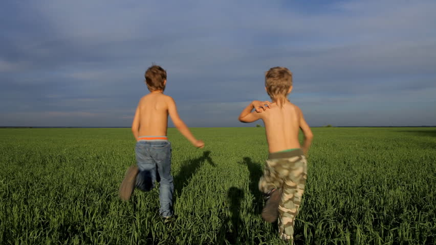 Two boys are playing tag in green field - HD stock footage clip