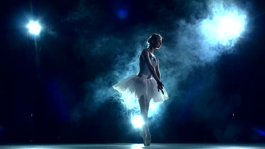 graceful ballerina doing a workout in the classroom. Smoke, fog, silhouette. ballet dancer in white tutu, girl in pointe, whirls around you. slow motion